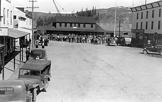 Crowds assembled outside of the Depot at the intersection of Front and Main Streets (c 1942)